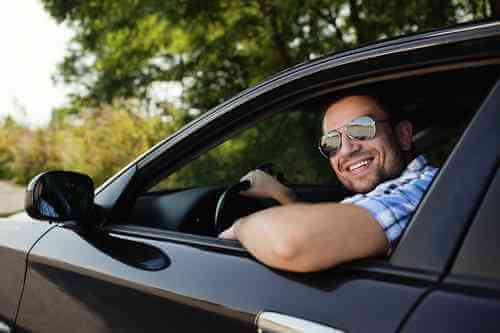 happy man in sunglasses driving car