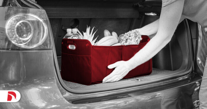 a person removes a basket full of grocery bags from the trunk