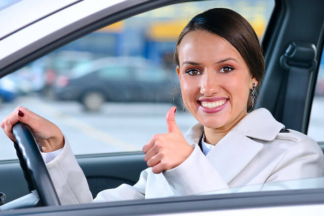 Woman in the driver's Seat giving thumbs Up