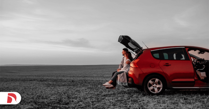 a couple sits in the back of their car starting out at a flat landscape