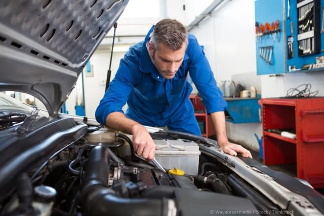 Mechanic examining under hood of car