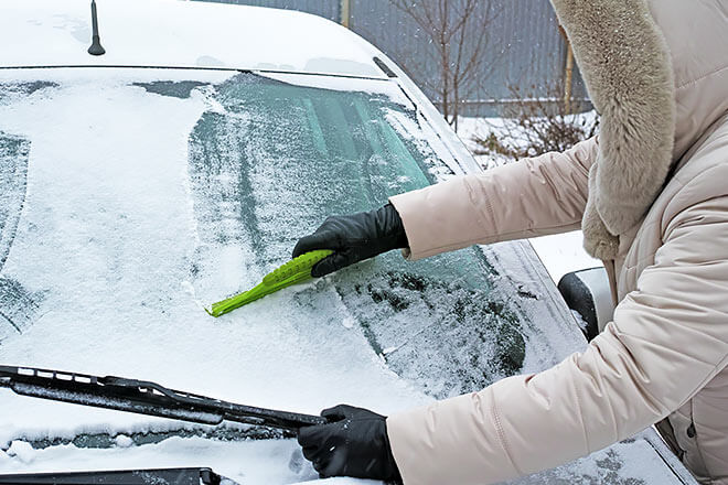 Person scraping ice on windshield