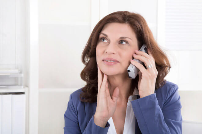 Older woman on the phone with her car insurance company, asking who to include on her car insurance policy