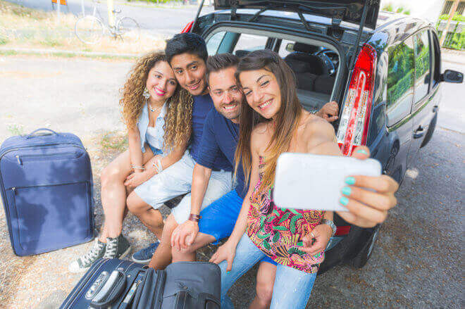 Group of friends taking a selfie before they go on road trip