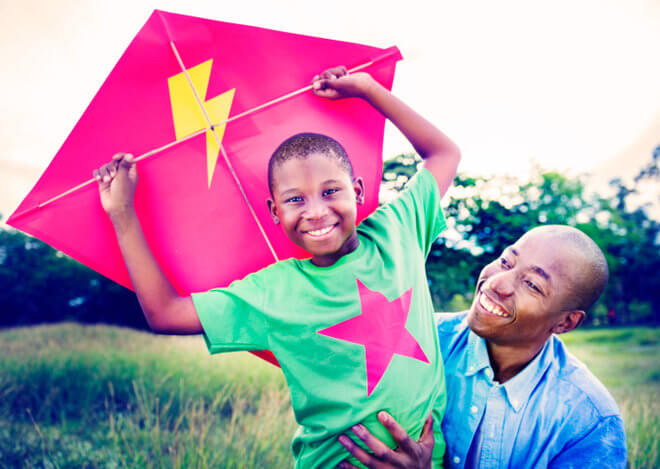 African American father and son smiling at one another, flying a bright red kite in green field