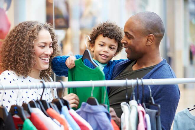 Happy African American family shopping for back to school clothes during tax-free weekend