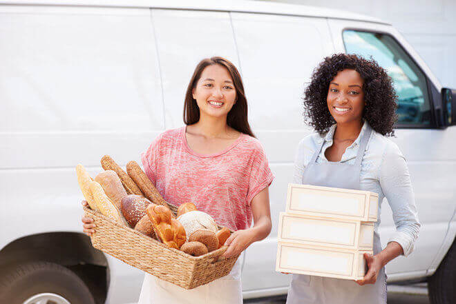 Two young women holding bakery goods, standing in front of white delivery van