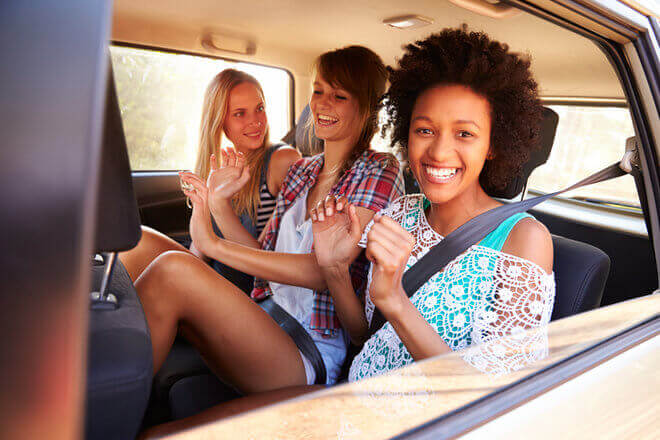 Three young women happily riding in the backseat of a car, ready for a summer roadtrip