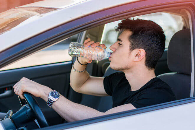 Young man drinking water bottle in car during the heat of the summer