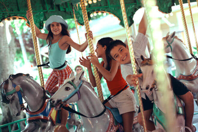 Three smiling children enjoying carousel at fair