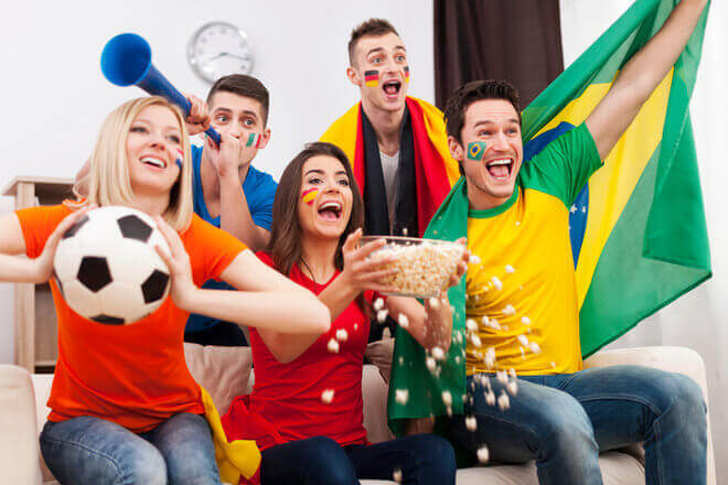 Group of diverse friends celebrating summer Olympics at home