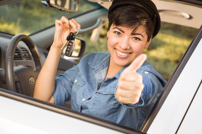 "Smiling young mixed race woman in car, holding car keys and giving a ""thumbs up"" to the camera"