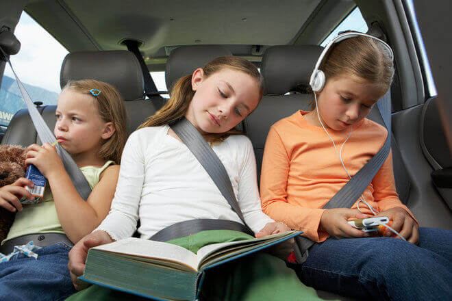 Three elementary-aged girls doing homework in the backseat of a car, with one reading, one listening to music, and one drinking a juice box