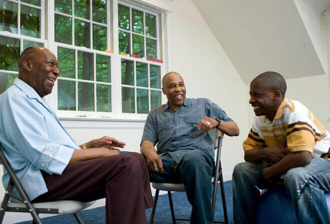 Three african american family members discussing term life insurance at home