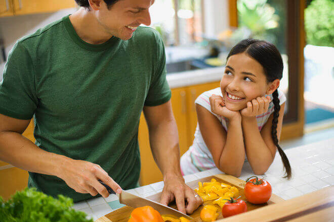 Hispanic father and daughter cooking together in kitchen, with dad chopping various colorful bell peppers and daughter smiling