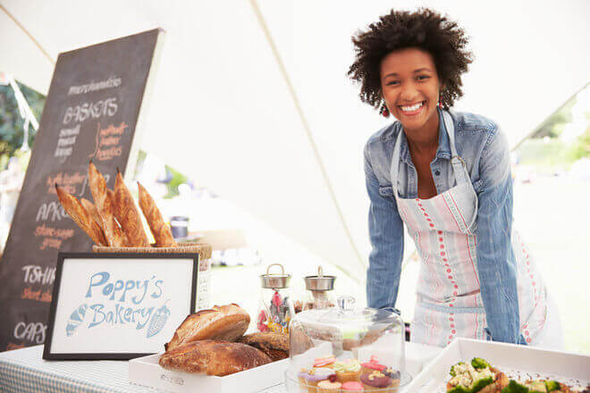 African American small business owner selling baked goods at local market
