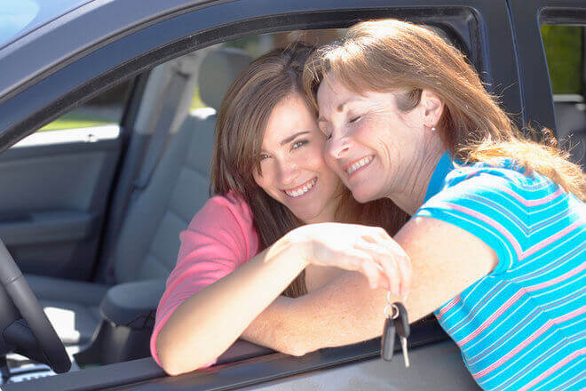 Mom reaching into car window to hug daughter, a new driver