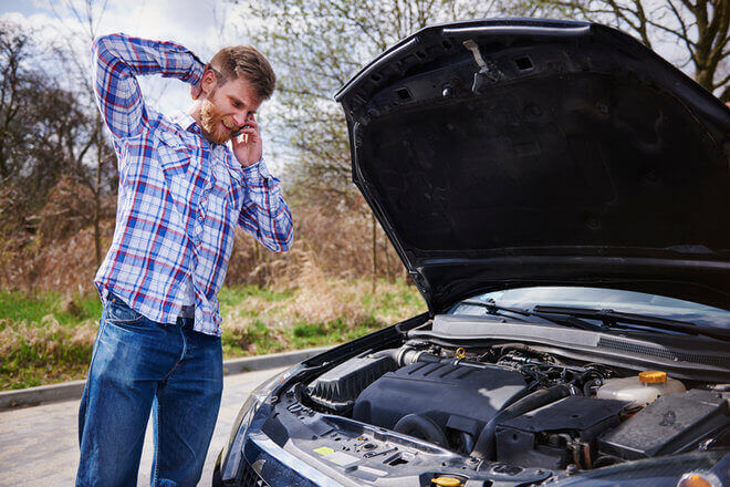 Blonde young man standing next to open hood of car, on cell phone, unsure of car problem