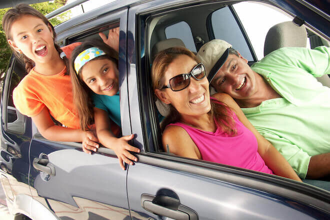 Family in SUV excited for a holiday road trip and playing fun road trip games