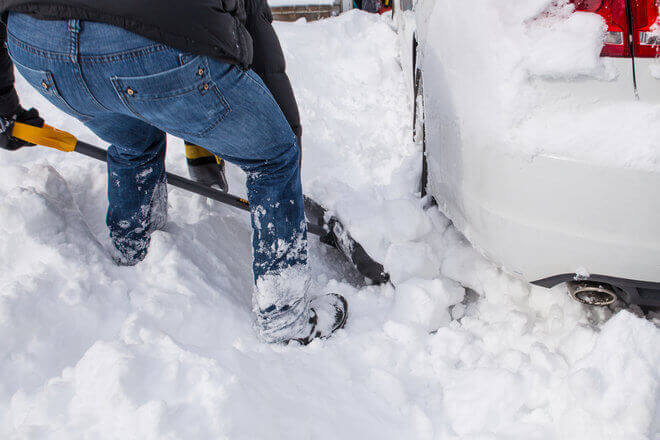 Man in jeans shoveling snow from around car tires, stuck in snow
