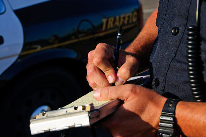 Close-up of traffic cop writing ticket for traffic violation