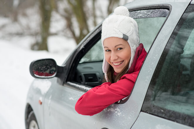 Woman looking out drivers side window with snow in the background