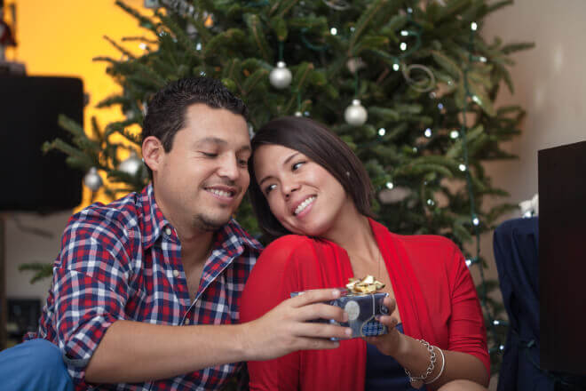 Happy couple exchanging Christmas gifts under a Christmas tree