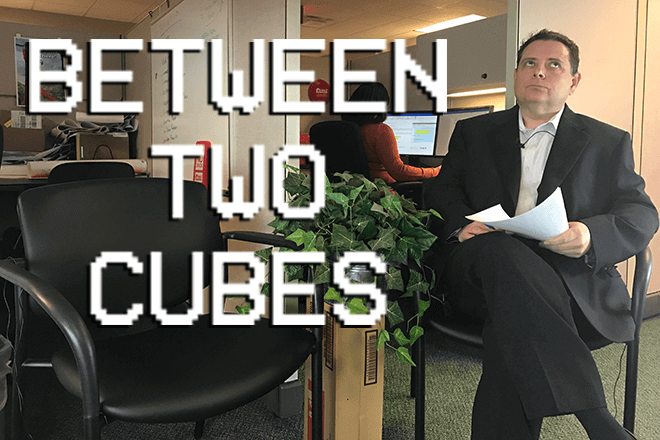 Man sitting in office chair at Direct Auto & Life Insurance headquarters, hosting Between Two Cubes video series