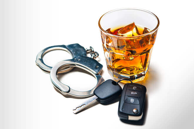Alcoholic beverage, hand cuffs, and car keys, pointing towards consequences of DUI or DWI