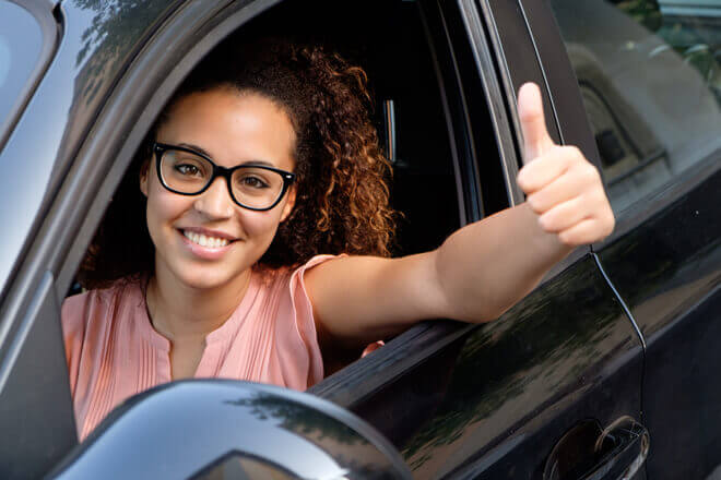 African American female driver with glasses, looking out her car window and giving the camera a thumbs up