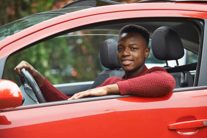 African American teen driver in red car, hitting the road for the first time