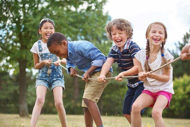 Kids laughing at a classic game of tug-of-war is the perfect touch for summer fun.