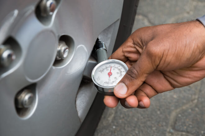 Before you hit the road, use a tire gauge to check your tire pressure.
