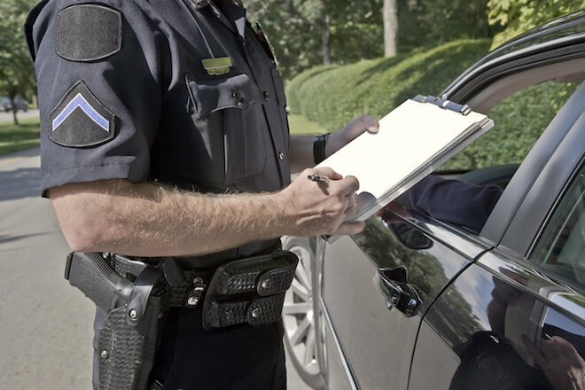Policeman writes a ticket for a car he pulled over.