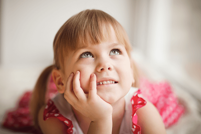little girl-smiling-hand-face-looking-up