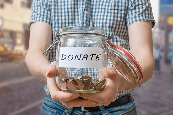 little-boy-holds-out-donation-jar