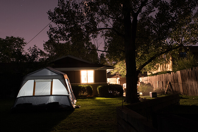 family camping in their backyard at night