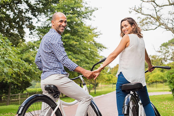 man and woman holding hands on bicycles while on a date in a park outdoors