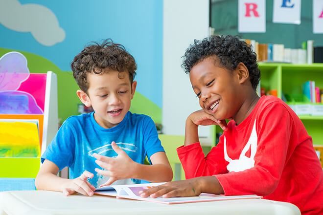 two smiling kids sitting at table in a bright, colorful room with a book