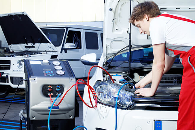 Car technician checking car's air conditioning (A/C)