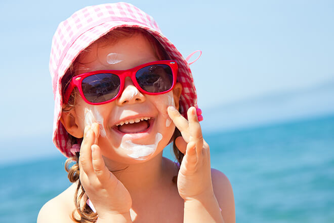 Kid smiling at the beach in sunglasses putting sunscreen on cheeks.
