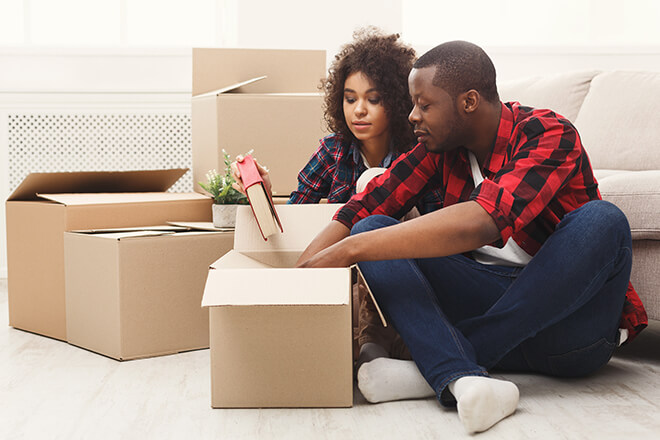 Couple sitting on floor unpacking moving boxes