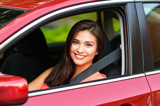 smiling woman in red car wondering how to lower car insurance