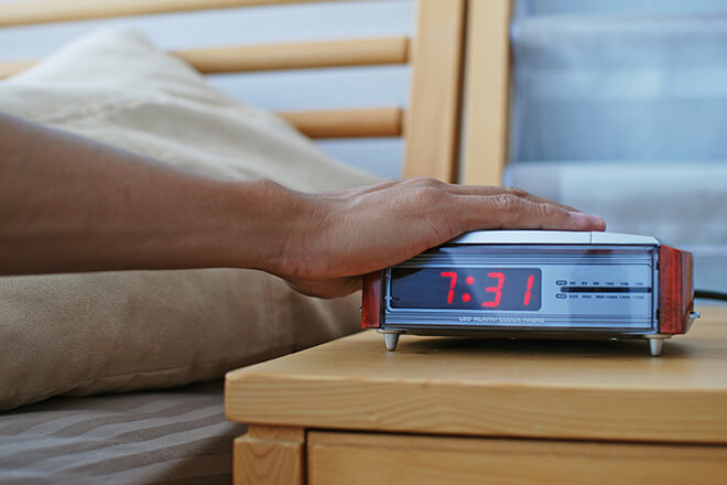 Hand reaching from bed to turn off or snooze alarm clock on nightstand