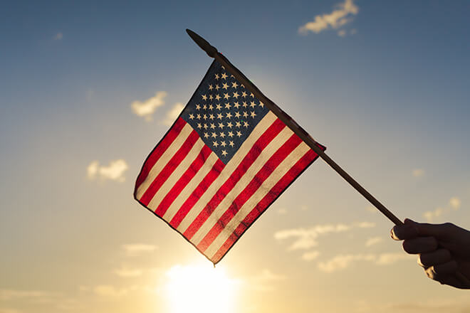 American flag with sun shining behind it in sky
