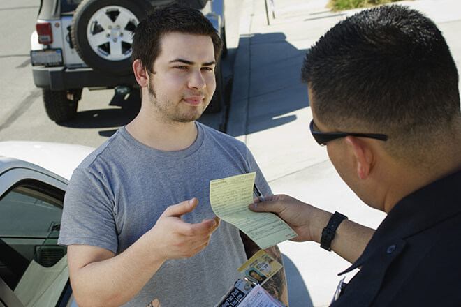 Police officer handing man a ticket