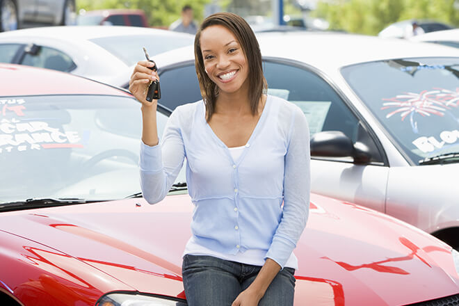Smiling woman holding car keys while sitting on hood of car