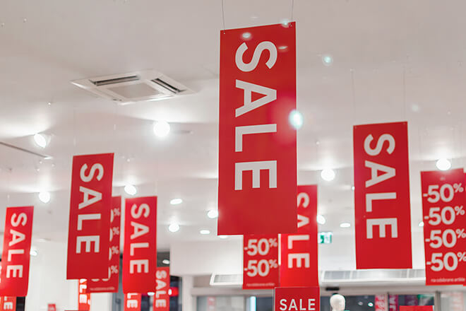 Red and white sale signs inside store for Black Friday