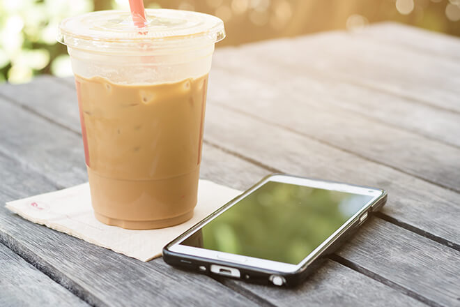 Cell phone on table next to cup of iced coffee