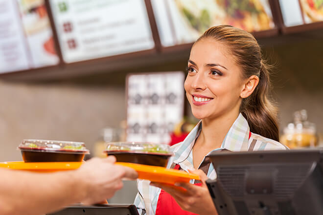 Smiling fast food worker handing tray to customer.
